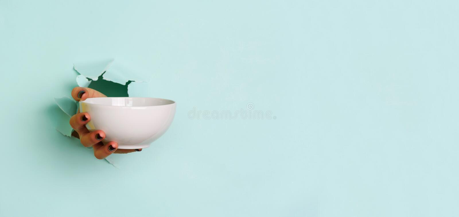 Female hand holding empty bowl on blue background with copy space. Healthy eating, dieting concept. Banner royalty free stock images
