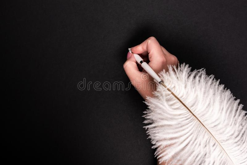 Female hand holding feather pen over black surface. Female hand holding feather pen over black background stock images