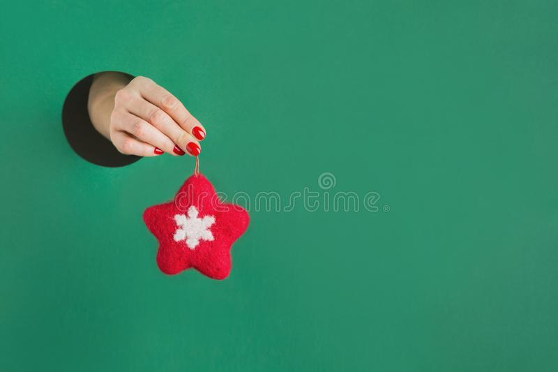 Female hand holding felt red star through round hole in green paper. Handmade toy. Christmas decor. Xmas greeting card stock images