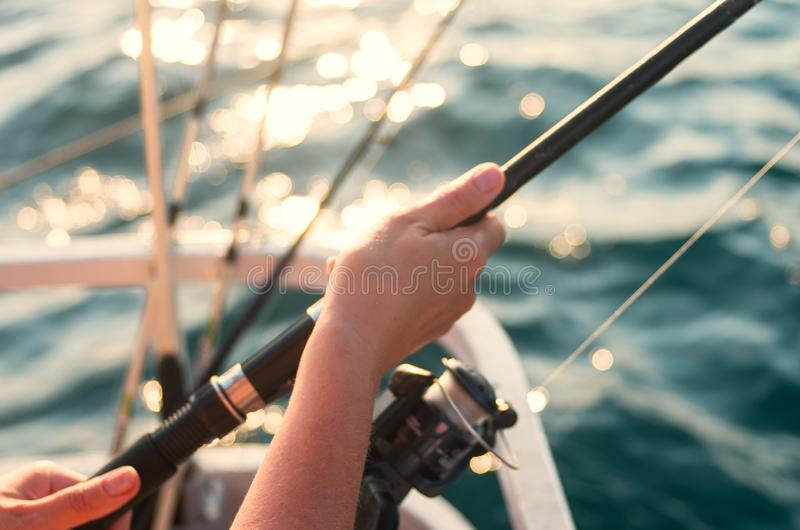 Female hand holding a fishing pole against the background of the sea. The woman is fishing. Female hand holding a fishing pole against the background of the sea stock photos
