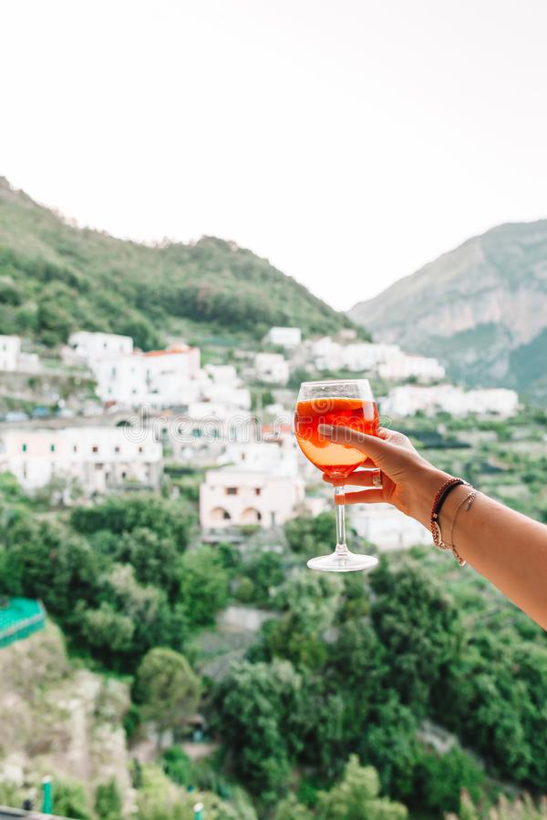 Female hand holding glass with Spritz Aperol alcohol drink background of beautiful old italian village on Amalfi coast. Glass with Spritz Aperol alcohol drink royalty free stock image