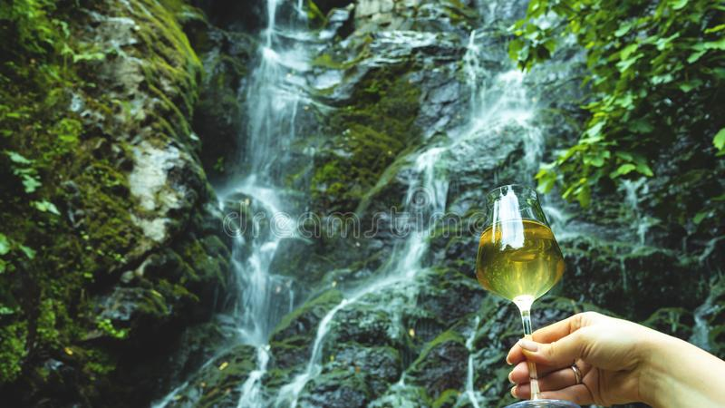 Female hand holding a glass of white wine in the background rock mountain with a waterfall.  royalty free stock photo