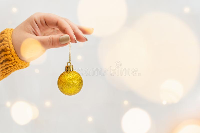 Female hand holding golden Christmas tree ball with garland bokeh on background. Woman hand in orange sweater holding golden Christmas tree ball with garland royalty free stock images