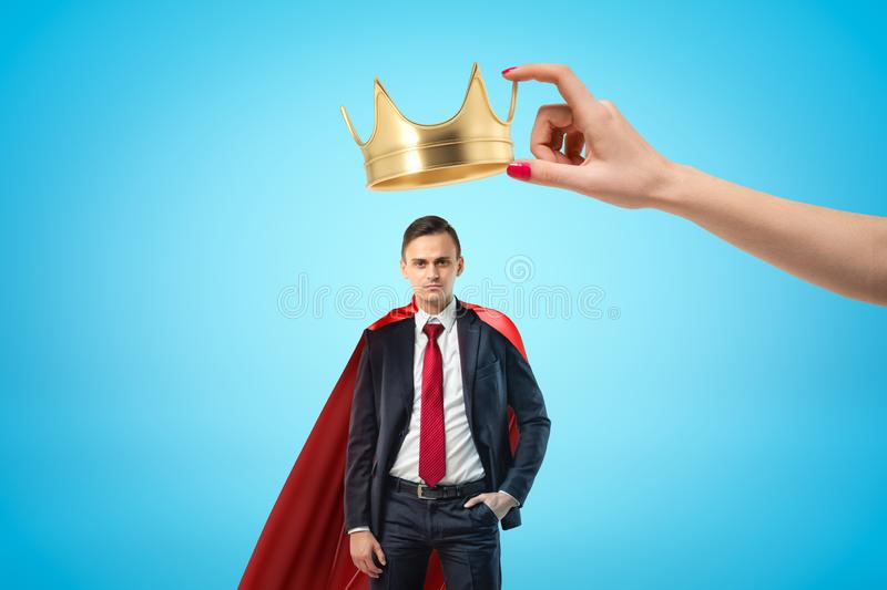 Female hand holding golden crown above young businessman with red cloak on blue background. Banking and finance. Business success. Fortune and glory royalty free stock photography