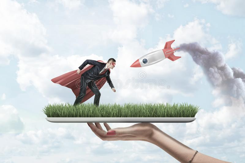 Female hand holding grass board with small businessman in red superman mask and cloak with silver red rocket on blue sky. Background. Success and strategy royalty free stock photography