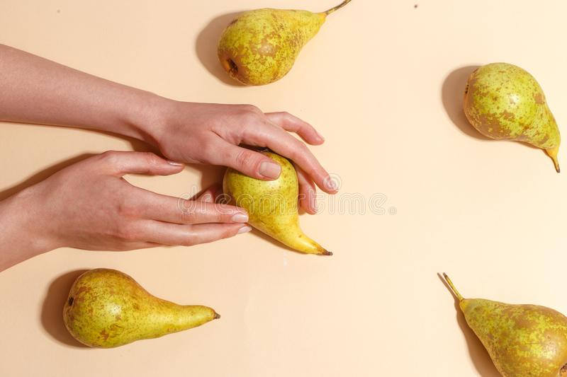 Female hand holding a green pear. Diet food fruit woman sweet organic human fresh nature tropical background vitamin delicious juicy natural healthy summer stock images