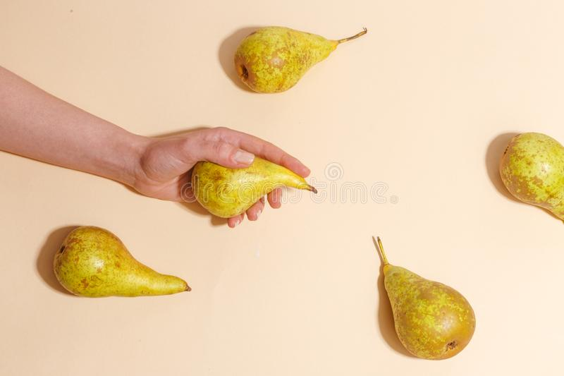 Female hand holding a green pear. Diet food fruit woman sweet organic human fresh nature tropical background vitamin delicious juicy natural healthy summer royalty free stock photo