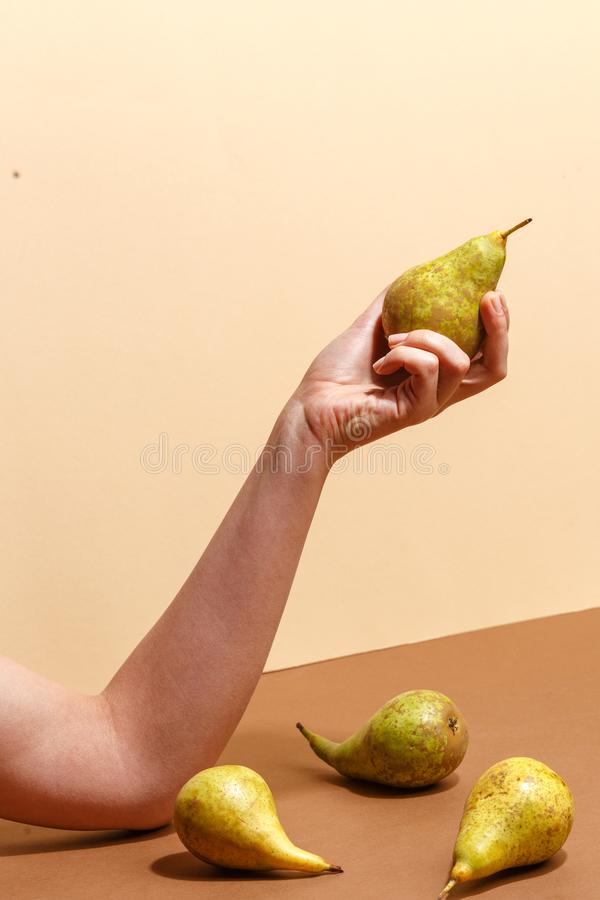 Female hand holding a green pear. Diet food fruit woman sweet organic human fresh nature tropical background vitamin delicious juicy natural healthy summer royalty free stock photography