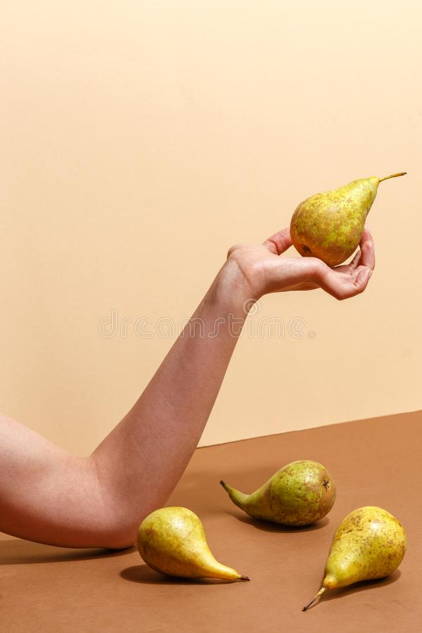 Female hand holding a green pear. Diet food fruit woman sweet organic human fresh nature tropical background vitamin delicious juicy natural healthy summer stock photography
