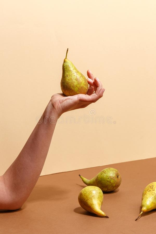 Female hand holding a green pear. Diet food fruit woman sweet organic human fresh nature tropical background vitamin delicious juicy natural healthy summer stock photo