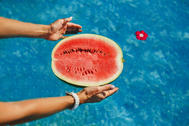 Female hand holding half of ripe juicy watermelon in the swimming pool. Freshness, Enjoyment Concept stock photography