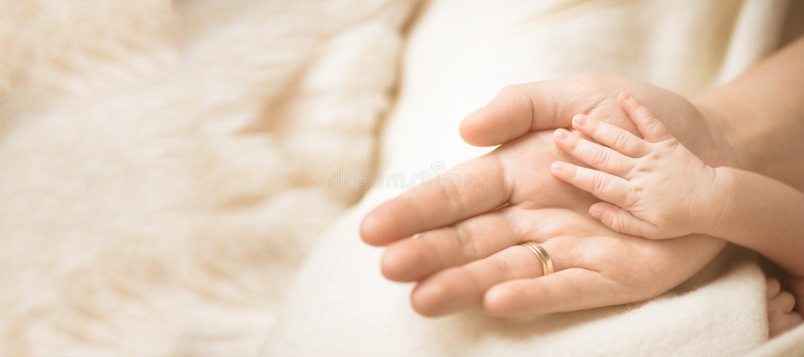 Female hand holding her newborn baby`s hand. Mom with her child. Maternity, family, birth concept. Copy space for your stock photos