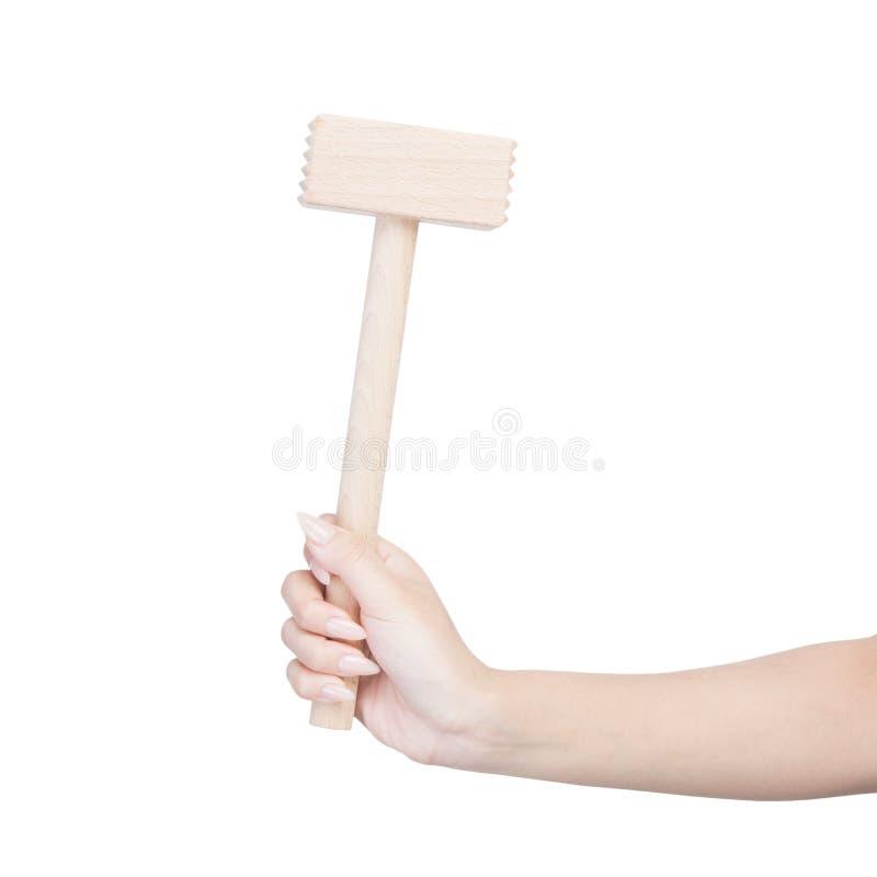 Female hand holding kitchen hammer. Isolated on white royalty free stock image