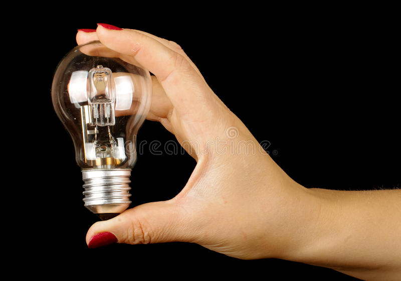 Female hand holding lamp isolated on the black background. Female hand holding different objects isolated on the black background stock images