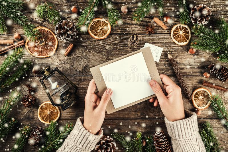 Female hand holding a letter to Santa on holiday wooden background with Christmas decoration, Fir branches, lamp, pine cones royalty free stock image