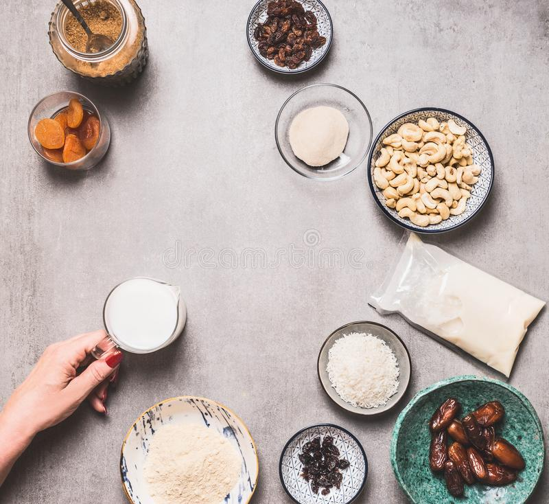 Female hand holding little jug with non dairy milk on concrete background with vegan gluten-free cake ingredients: cashew , almond. Flour, Coconut cream and stock photography