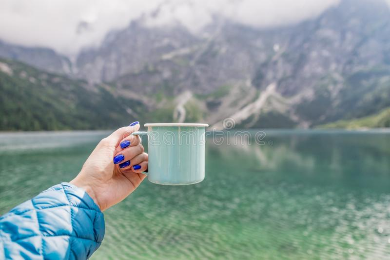 Female hand holding mint color enamel cup. Crystal clear lake and mountains. Tatra National park, Poland. Famous lake royalty free stock image