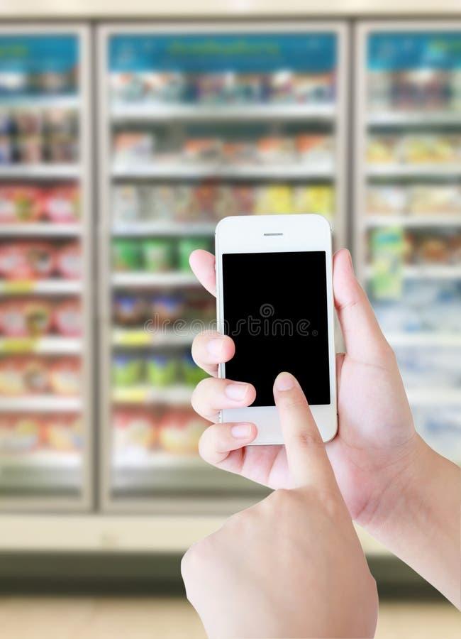 Female hand holding mobile smart phone on Supermarket. Freezer blur background, business concept stock photo