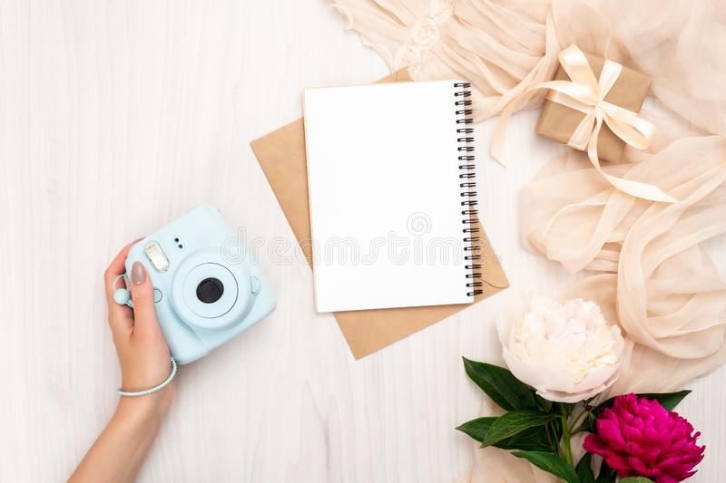 Female hand holding modern camera on a wooden background with peonies flowers. Top view, tender minimal flat lay style composition royalty free stock photography