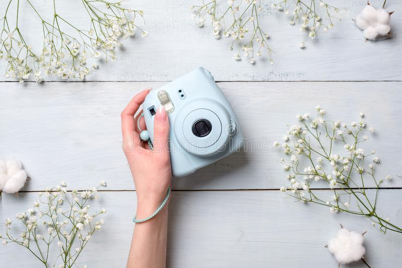 Female hand holding modern polaroid camera on a blue wooden background with flowers. Top view, tender minimal flat lay style compo stock images