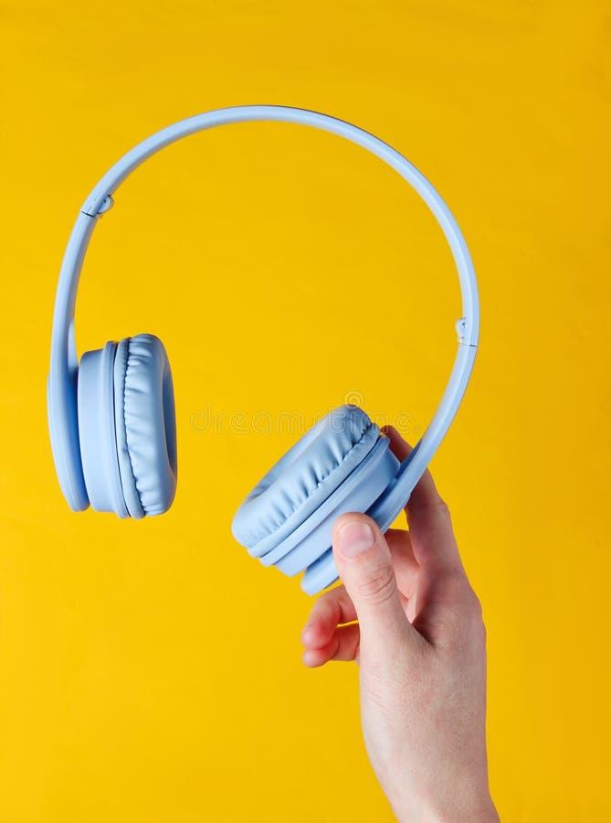 Female hand holding modern wireless blue headphones. On yellow background stock photo