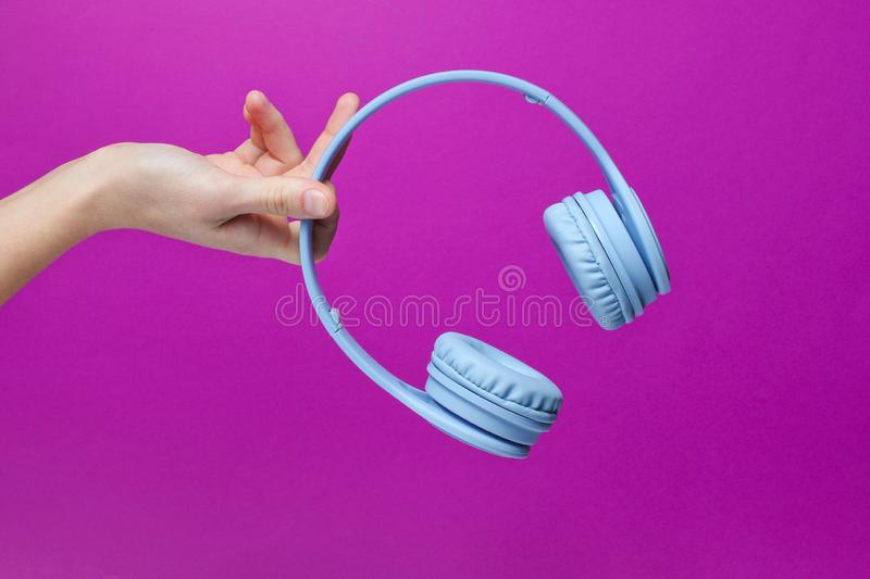 Female hand holding modern wireless blue headphones. On a pink background royalty free stock photos