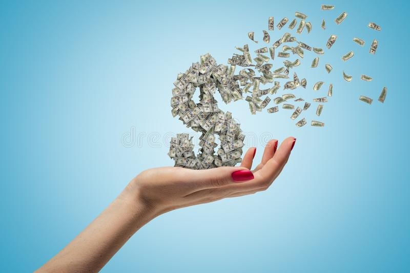Female hand holding money dollar sign shattering on blue background. Money and finance. Banking and financial industry. Management and savings royalty free stock images