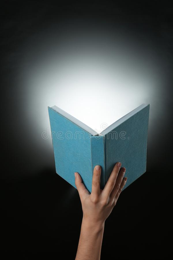 Female hand holding open book with glowing on dark background stock photos