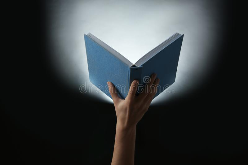 Female hand holding open book with glowing on dark background royalty free stock images