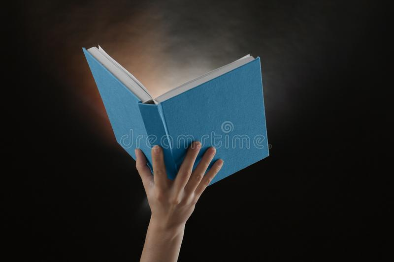 Female hand holding open book with glowing on dark background stock photography