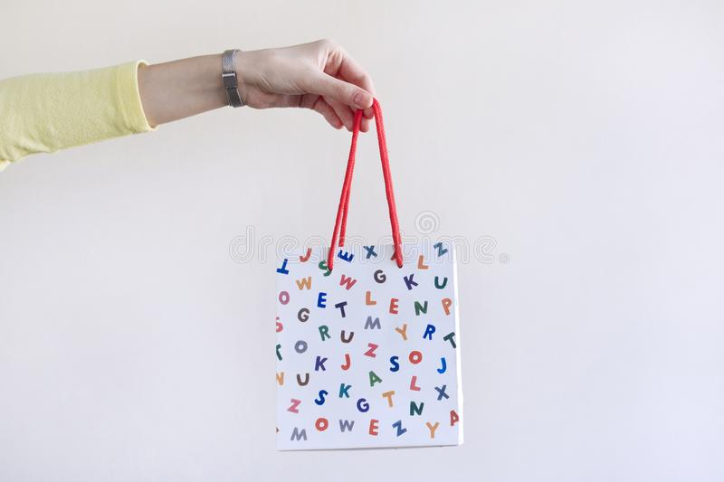 Female hand holding paper shopping bag on white background. royalty free stock images