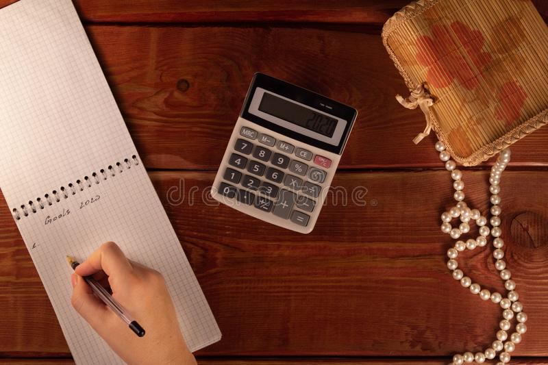 Female hand holding pen on open notepad. Woman writes goals for new year 2020. Calculator, pearl necklace on wooden table. Concept royalty free stock photography