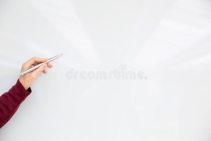 Female hand holding pen and pointing to the white board for new project presentation stock photography