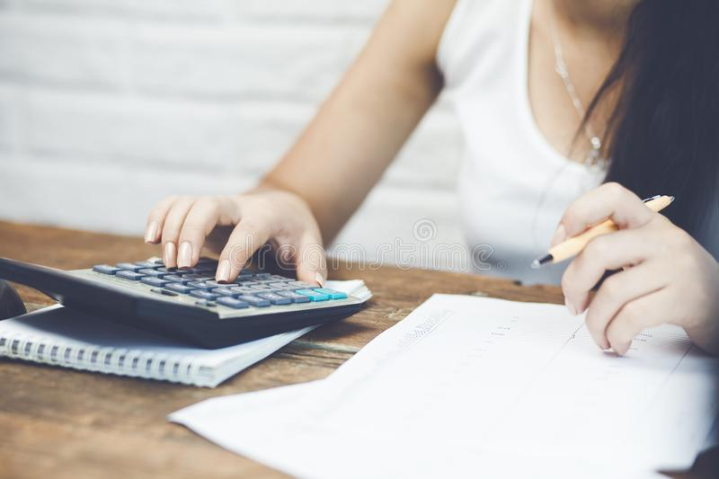 Female hand holding a pen and using calculator royalty free stock photo