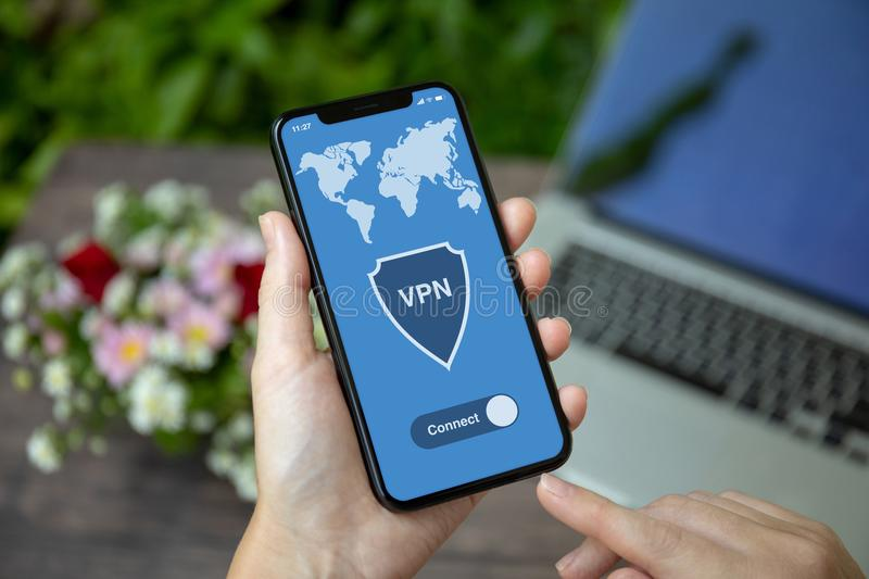 Female hand holding phone with app vpn creation Internet protocols. For protection private network royalty free stock images