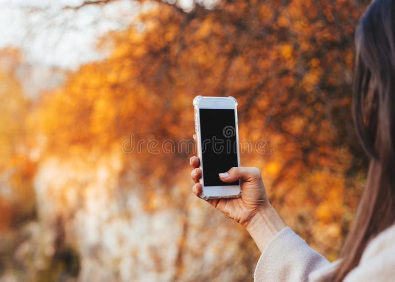 Female hand holding a phone, black screen stock photography