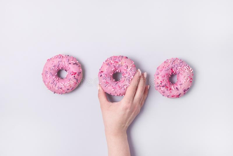 Female Hand Holding Pink Donut Donuts With Icing on Pastel Pink Blue Background Sweet Tasty Donuts Copy Space Top View Flat Lay stock photo