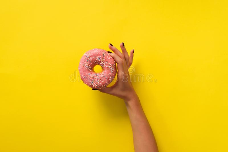 Female hand holding pink donut over yellow background. Top view, flat lay. Sweet, dessert, diet concept. Banner with copy space. stock photos