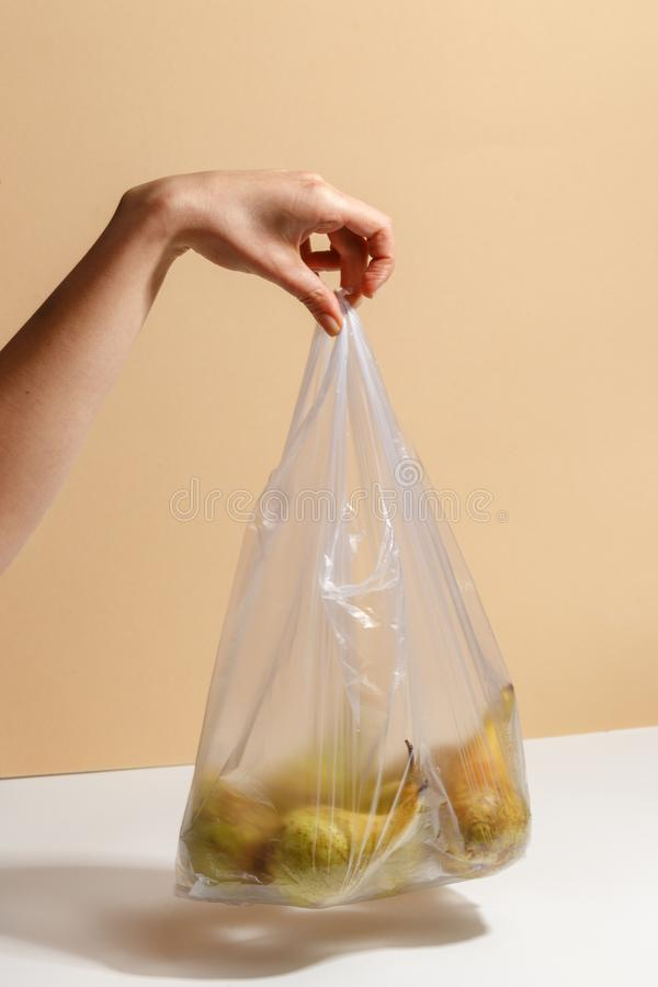 Female hand holding a plastic bag with pears. Green diet food fruit woman sweet organic human fresh nature tropical background vitamin delicious juicy natural royalty free stock photo