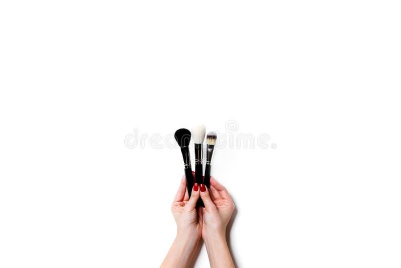 Female hand holding professional make-up brushe isolated on white background. royalty free stock photos