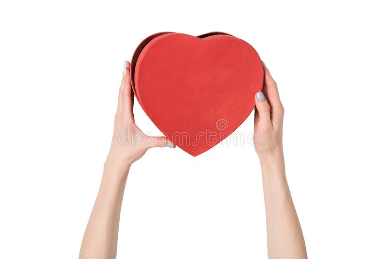 Female hand holding a red box in the shape of a heart. Isolate on white background royalty free stock photos