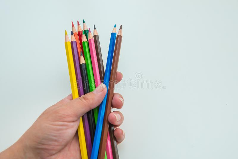 Female hand holding a set of colored pencils on light gray background, copy space. Drawing and education theme.  stock photography