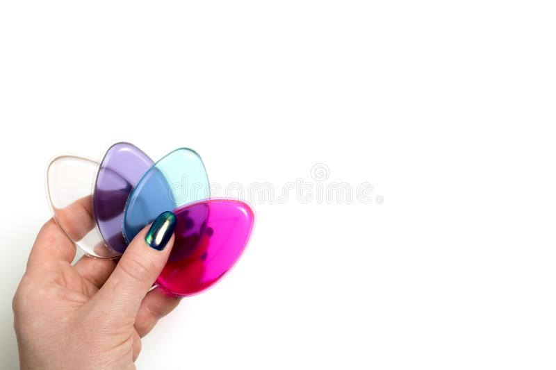 Female hand holding silicone cosmetic sponges on a white background. Female hand holding colorful silicone cosmetic sponges on a white background royalty free stock photography