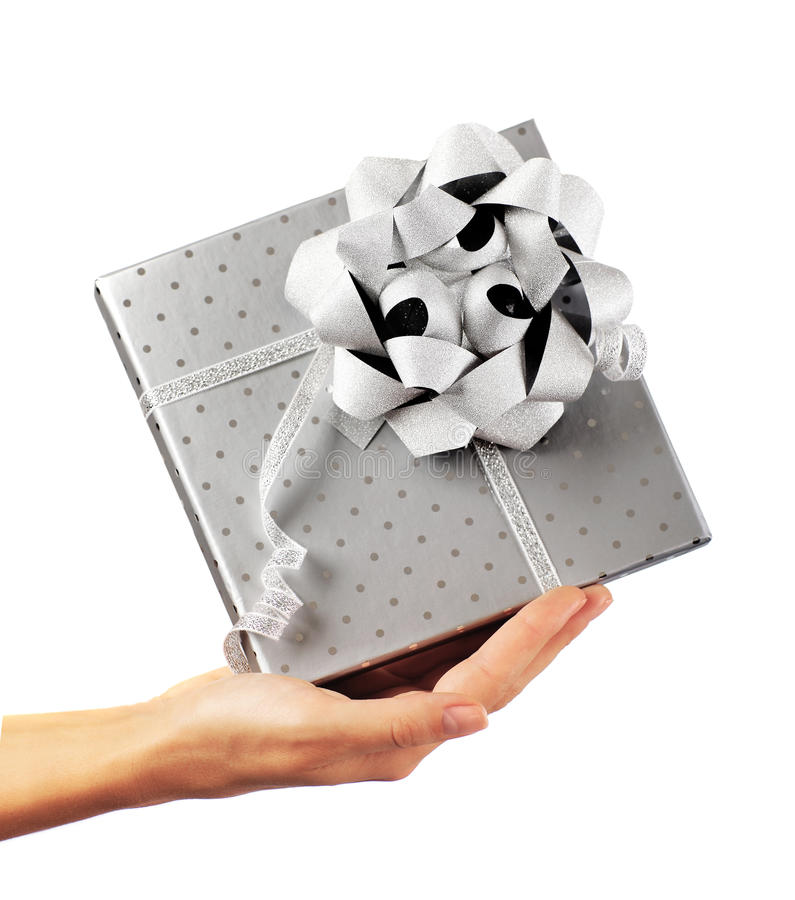 Female hand holding silver gift box stock image