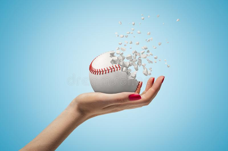 Female hand holding small baseball ball shattering into pieces on blue background royalty free stock images