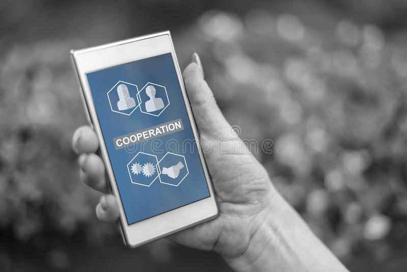 Cooperation concept on a smartphone. Female hand holding a smartphone with cooperation concept stock illustration