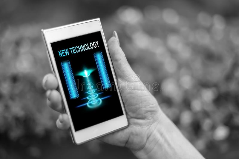 New technology concept on a smartphone. Female hand holding a smartphone with new technology concept royalty free stock photography