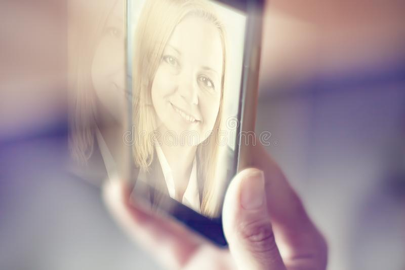 Female hand holding a smartphone with a portrait of a beautiful woman. Soft toning stock image