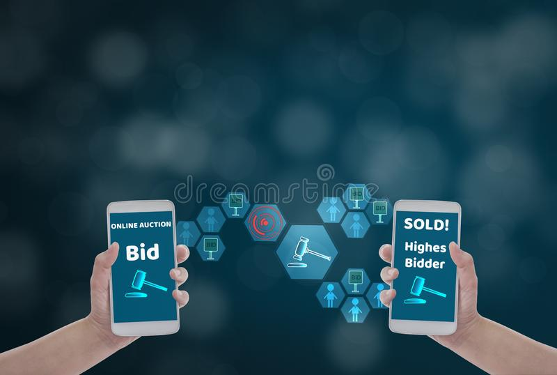 Female hand holding smartphone to Enter the price for bid,via wireless network on blue bokeh background with auction icon, Concept. Online auction via website royalty free stock image