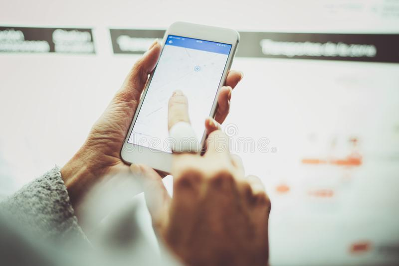 Female hand holding smartphone and using internet for looking new way on electronic city map with night modern blurred stock images